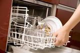 食器洗い機から食器を取り出す女性の手元