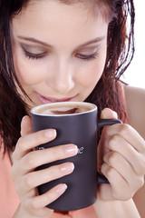 Genussvoll Kaffee trinken, junge Frau trinkt mit Lächeln