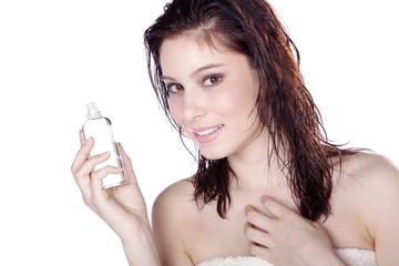 Hübsche Frau präsentiert freundlich Massage Öl, quer