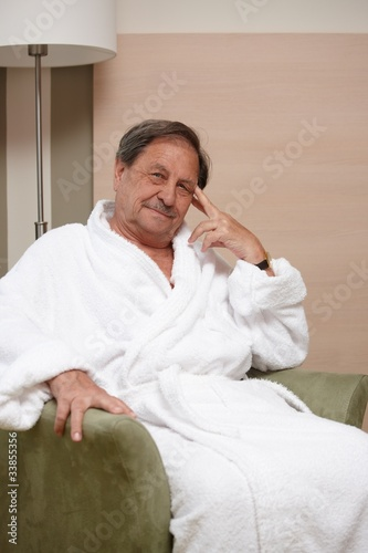 Happy elderly man in armchair