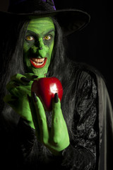 Evil witch with her poisonous red apple, dark background.