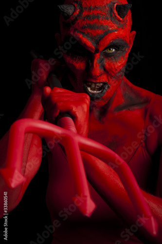 Devil attacking with her trident, black background.