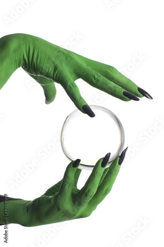 Green witch's hand holding crystal ball, white background.