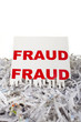 Fraud being put through a shredder, white background.