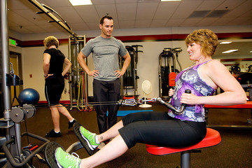 Personal Trainer helping exercise at gym