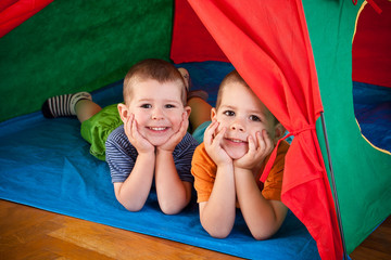 Little boys lying inside colorful tent