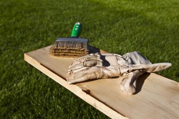 Holzlatte mit Pinsel lasieren und arbeitshandschuh