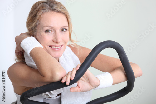 Blond woman on exercise bike in gym