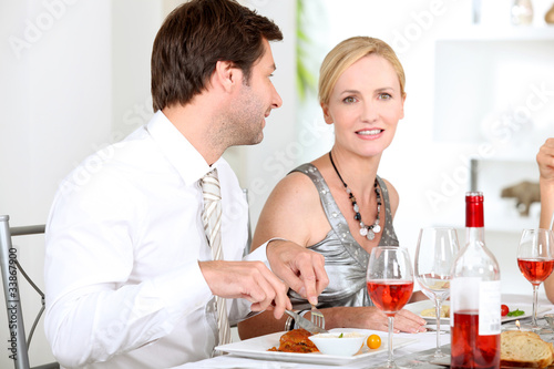 Couple sat at table eating meal and drinking wine