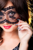 Attractive brunette girl with lacy mask on her eyes