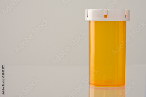 Closeup of empty medicine bottle with reflection.