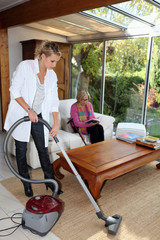 Girl vacuuming for an elderly woman
