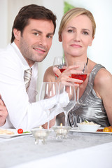 Romantic couple enjoying rose wine with dinner