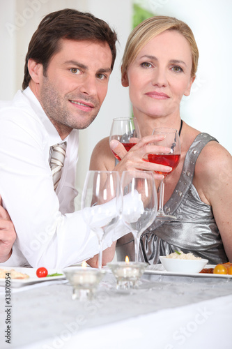 Romantic couple enjoying rose wine with dinner