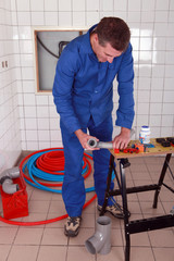 Plumber using a workbench