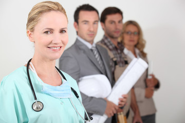Female nurse stood next to four professionals from different