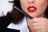 Closeup of a businesswoman with red lipstick holding a pen
