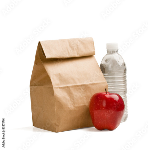 Brown lunch bag, red apple and bottle of water isolated on white