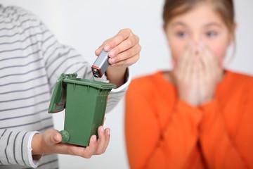 Closeup of a boy putting a battery in a miniature bin