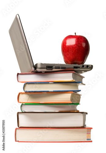 Red apple and computer on top of school books.