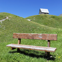 chapel and bench in alpine mountain in summer