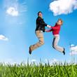 Junges Paar springt glücklich auf Wiese