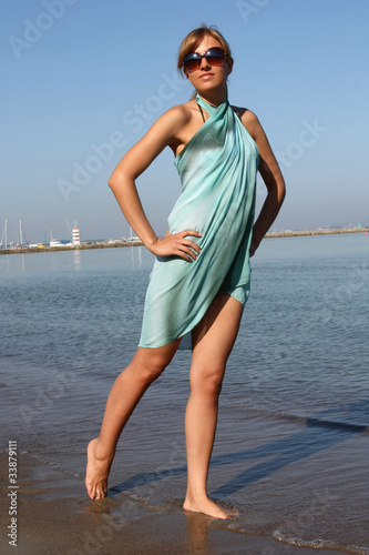 Woman in dress and sunglasses on the beach