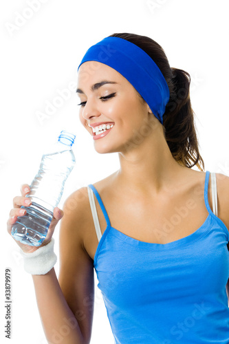Happy woman in sportswear drinking water, isolated on white