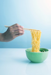 yellow noodle soup in bowl and chopstick