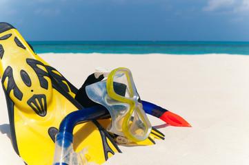 Taucherbrille und Flossen am Strand