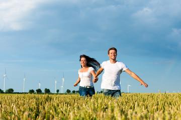 Glückliches Paar läuft auf über ein Kornfeld