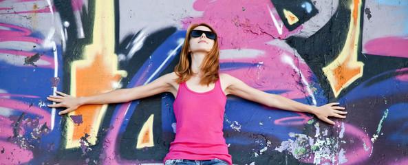 Style girl near graffiti wall.