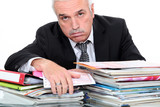 Grey hairy man looking fed up in front of paper work