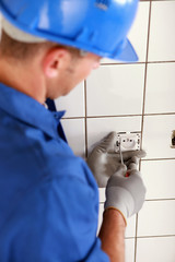 Man fitting a two pin electric socket