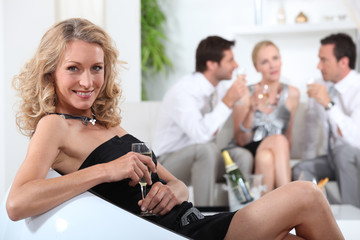 Profile of blond woman sitting holding champagne glass