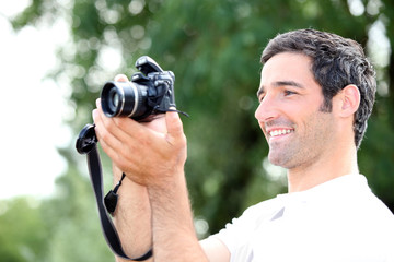 Happy relaxed man looking at the screen of his DSLR camera