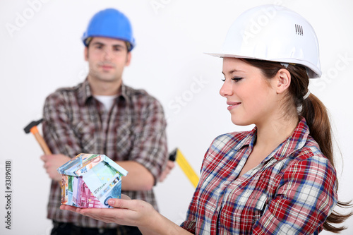 Female and male construction worker holding house