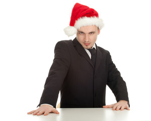 standing serious businessman in red Christmas hat