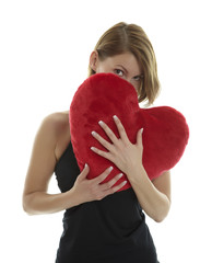 Woman hiding behind heart pillow