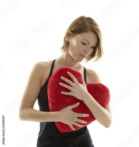 Woman cuddling with heart pillow