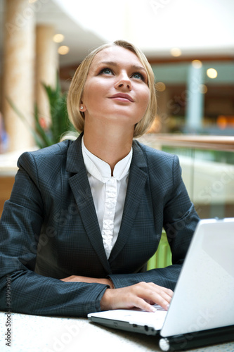 Portrait of a pretty businesswoman sitting at cafe with a laptop