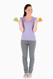 Good looking woman holding fruits while standing
