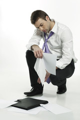 disappointed young businessman picking up files from the floor