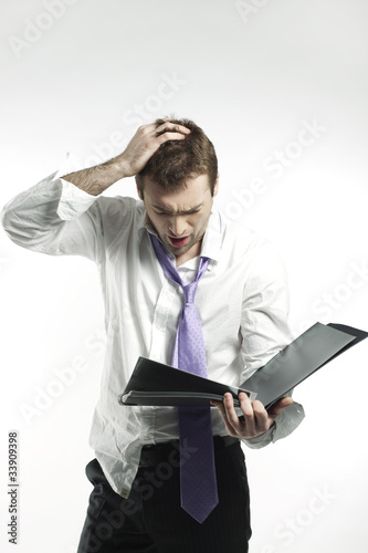 businessman looking at business report with desperation