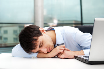 Portrait of a tired young business man sleeping on the table