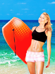 Happy sporty girl playing body board on the beach