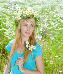The happy young woman in a wreath from wild flowers