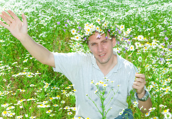 man in a wreath from wild flowers in the field of camomiles