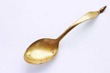 Brass spoon on  white background.