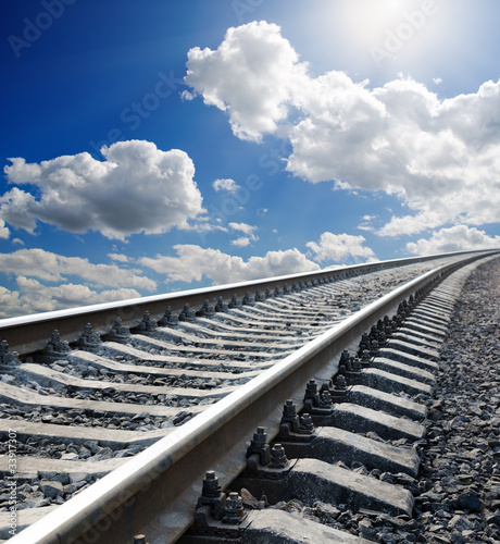 railway to horizon under cloudy sky with sun